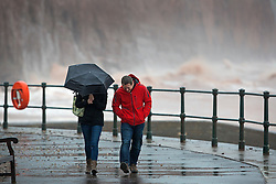 © Licensed to London News Pictures. 27/01/2016. Sidmouth, UK.  A couple walk on the seafront at Sidmouth as the tail end of storm Jonas hits the UK. Photo credit: Peter Macdiarmid/LNP