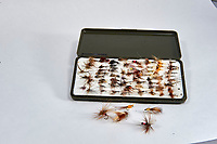 Box of trout fishing flies against a white background