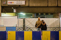 24 march 2016 Brussels Belgium. After the terrorist attacks in Brussels. Flowers and candles at the still closed subway entrance, where police fences close the entrance. A man and woman grieve late at night at the entrance.