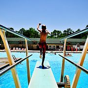 A boy jumps off the diving board at Bryan Park Pool in Bloomington, Indiana.
