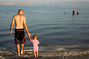 Israel, Lower Galilees, Summer Vacation at the Sea of Galilee Man and his daughter enter the lake. Model Release Available