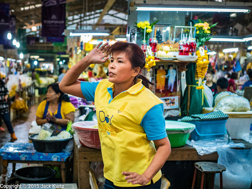 """21 DECEMBER 2015 - BANGKOK, THAILAND: A woman participates in an aerobics class in Pak Khlong Talat, also called the Flower Market. The market has been a Bangkok landmark for more than 50 years and is the largest wholesale flower market in Bangkok. Aerobics classes and fitness programs are common in Thai markets and parks. A recent renovation resulted in many stalls being closed to make room for chain restaurants to attract tourists. Now Bangkok city officials are threatening to evict sidewalk vendors who line the outside of the market. Evicting the sidewalk vendors is a part of a citywide effort to """"clean up"""" Bangkok.       PHOTO BY JACK KURTZ"""