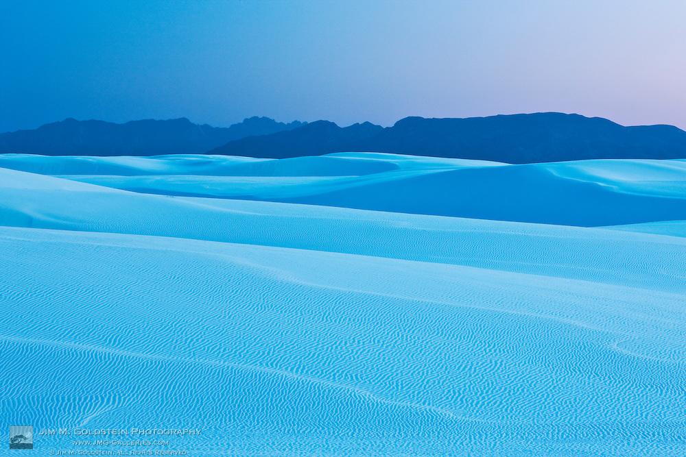 Dusk light falls across the vast desert landscape of White Sands National Monument, New Mexico