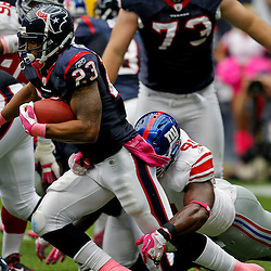 October 10, 2010; Houston, TX USA; Houston Texans running back Arian Foster (23) is tackled by New York Giants defensive end Justin Tuck (91) during the first half at Reliant Stadium. Mandatory Credit: Derick E. Hingle