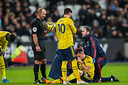 Mike Dean (Referee) holding the ball as Granit Xhaka (Arsenal) receives treatment for an injury during the Premier League match between West Ham United and Arsenal at the London Stadium, London, England on 9 December 2019.