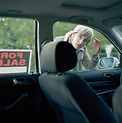 Young woman looking in window of car with 'For Sale' sign in window