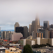 The Transamerica pyramid and other buildings of downtown San Francisco disappear into the fog on a partially overcast day. As seen from Russian Hill.