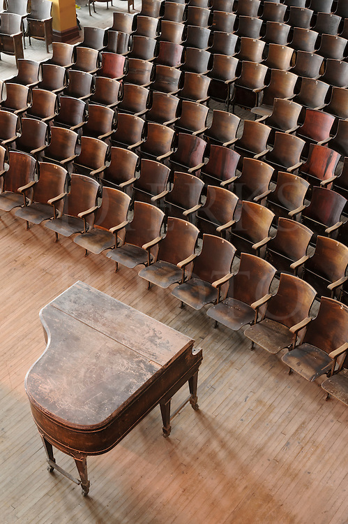 Empty concert hall or high school auditorium with old grand piano and wooden seats, very bad condition, viewed from above.