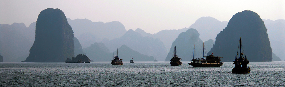 Vietnam: Ha Long Bay.Sailing junks ply their way between the Karst limestone peaks that jut from the South China Sea.