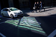 In an area of reflected light, a Toyota Hybrid car stops at traffic lights while businessmen walk along Threadneedle Street in the City of London - the capital's financial centre (aka The Square Mile), on 27th September 2018, in London, England.