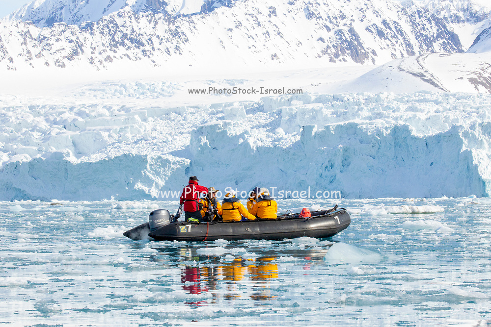 Adventure cruise passengers on a rubber zodiac dingy tour an iceberg in Spitsbergen, Norway in June
