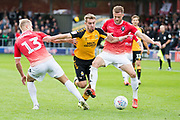 Salford City midfielder Sam Hughes and Salford City defender Scott Wiseman tackles the opponent during the EFL Sky Bet League 2 match between Salford City and Cambridge United at Moor Lane, Salford, United Kingdom on 12 October 2019.