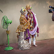 A couple pose for the videographer after their Oriya wedding. Elaborately crafted headgear, which resembles a peacock feather, is used by both the bride and the groom. Bhubaneshwar, Odisha (Orissa), 2012