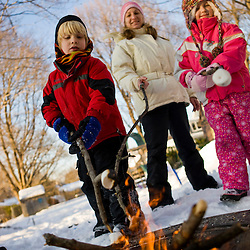 A woman and two kids toast marshmallows over a fire in a backyard in Portsmouth, New Hampshire.  Winter.