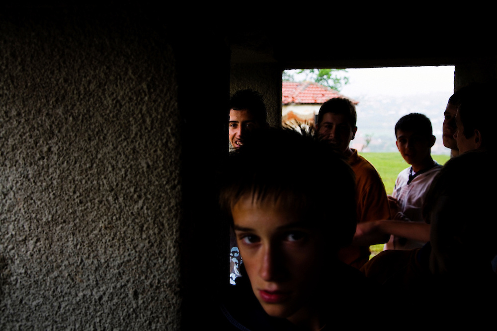 Albanian boys take shelter from a sudden rainstorm at a school above Shtime, Kosovo.