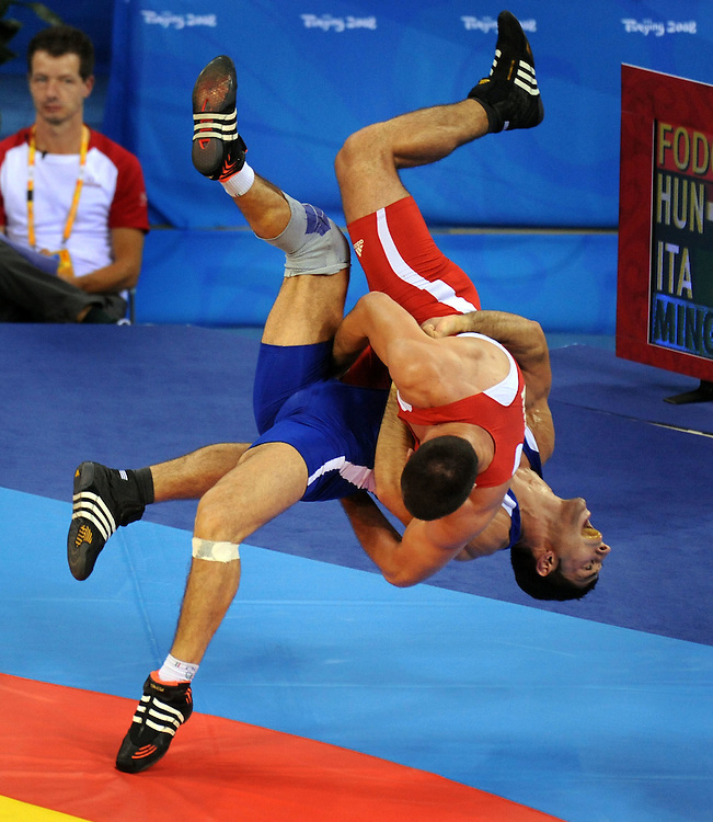 2008 OLYMPIC GAMES  - GRECO ROMAN WRESTLING  - 081408 - Italy's Andrea Minguzzi (blue) throws Zoltan Fodor of Hungary in the 84 kg Greco Roman wrestling.