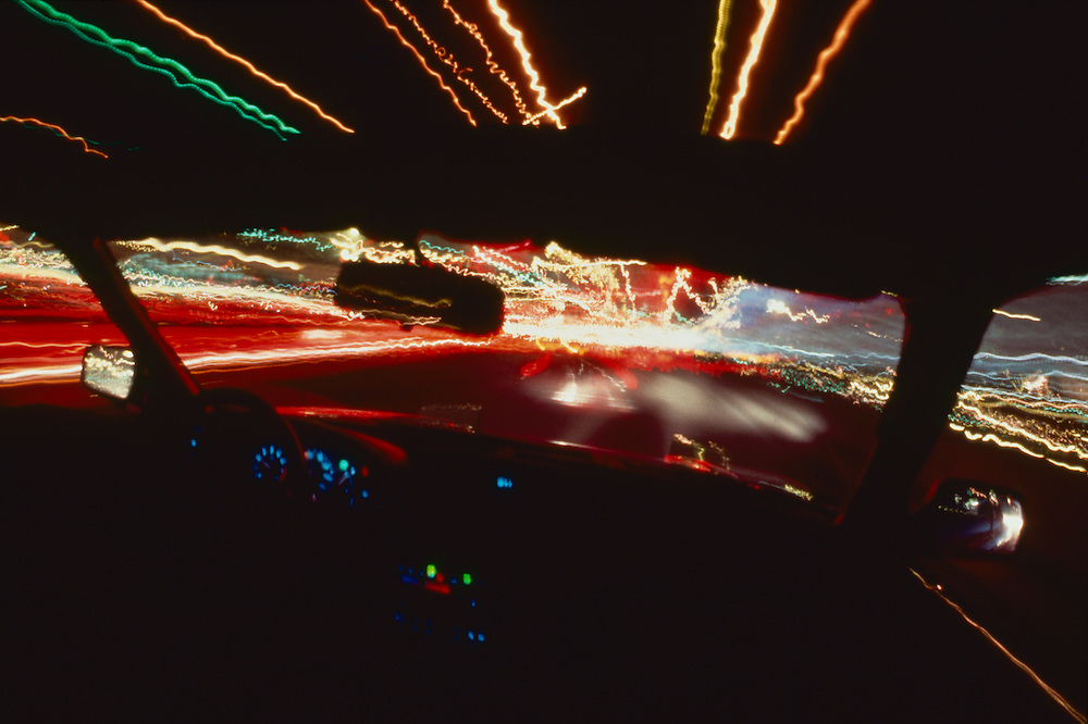 Lights streaking by from inside car, at night.