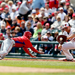 Mar 3, 2013; Sarasota, FL, USA; Philadelphia Phillies center fielder Ben Revere (2) dives as Baltimore Orioles first baseman Chris Davis (19) makes an attempt to pickoff  during the top of the first inning of a spring training game at Ed Smith Stadium. Mandatory Credit: Derick E. Hingle-USA TODAY Sports
