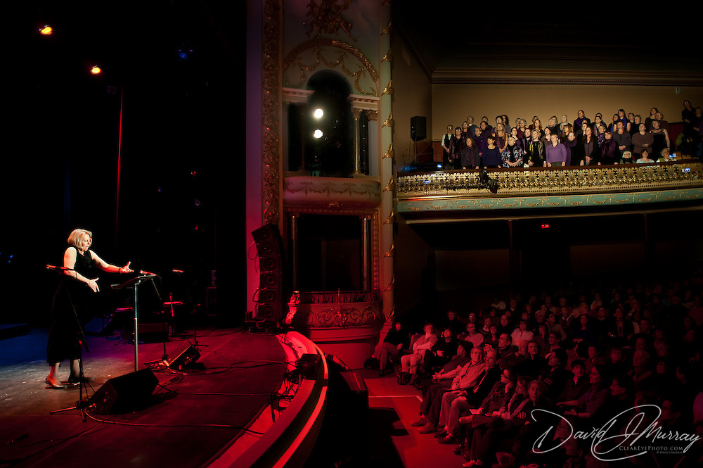 Portsmouth chorus Voices From The Heart, lead by Joanne Connolly (on stage), performs from the balcony at the start of a concert by the Soweto Gospel Choir at The Music Hall in Portsmouth, NH