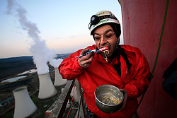 CZECH REPUBLIC PRUNEROV 22MAR10 - Greenpeace activist enjoys a meal atop the 300 metre high smokestack of the Prunerov II brown coal-fired power station. The 12 protesters have hung a banner saying 'Global Shame' highlighting Prunerov II as the largest source of carbon dioxide emissions pollution in the Czech Republic...jre/Photo by Jiri Rezac / GREENPEACE