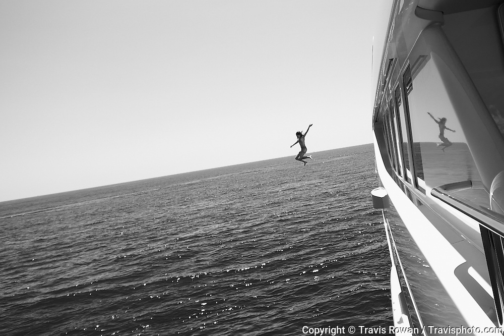 A woman jumps from a large private yacht into the blue waters of the Mediterranean Sea.