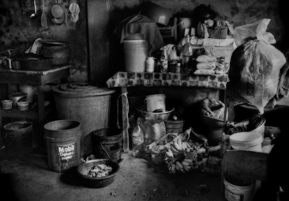 """It is through the kitchen and diet that petroleum contamination most often enters residents' bodies who live near oil exploration sites.  Teresa Ogona Flores' kitchen, typical of the standard of living for the Mestizo migrants who have settled along Via Auca in the past 3 decades.  South of Coca, Ecuador.<br /> <br /> Via Auca is a road that extends south from the city of Coca.  Coca began as a solitary airstrip for a military outpost in the mid-1960's.  The Huaorani were referred to as the """"Aucas"""" or """"savages"""" by their indigenous neighbors, the Kichwa.  The Via Auca, which extends south from Coca opened up territory where the """"uncontacted"""" lived."""