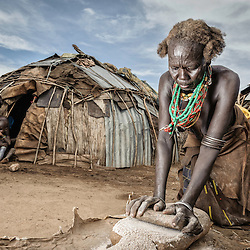 Dassanech woman grinding maize, Omo valley, Ethiopia, Africa