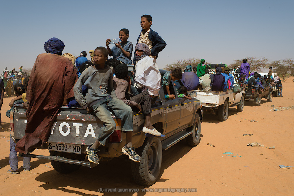 Malian refugees sit packed into pick-ups as they stand parked in the heat on the edge of the Mbera refugee camp in Mauritania while waiting for the rest of their convoy to catch up, on 6 March 2013. According to local NGO, ALPD, 825 refugees arrived in this convoy, packed into three trucks and an assortment of four wheel drive pick-ups.