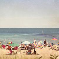 Beachgoers and sunbathers on the beach during summer.