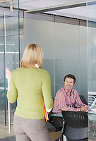 Two office workers talking in office