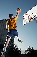 Young man with basketball jumping towards hoop mid-air
