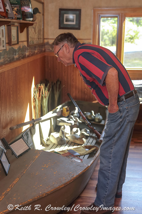Fritz Barnes examines the display of Gordon MacQuarrie memorabilia he helped create. Barnes donated the duck boat and several of the other MacQuarrie items on display.