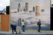 People awaiting a bus stand beneath a property developer's billboard showing a large aerial image of London skyscrapers in low cloud.