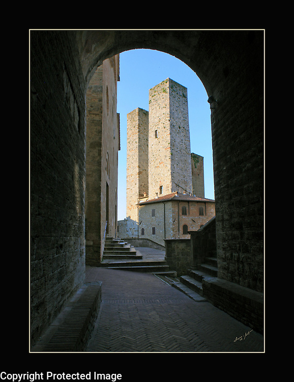 Watch towers in San Gimignano are framed by an archway to focus attention on the towers in the background.
