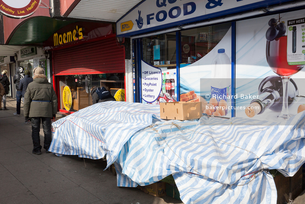 As the second week of the Coronavirus lockdown continues around the capital, and the UK death toll rising by 563 to 2,325, with 800,000 reported cases of Covid-19 worldwide, socially distancing shoppers queue outside a local shop for essentials in Brixton, on 1st April 2020, in London, England.