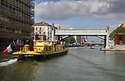 Pont Levant de la Rue de Crimee, over the Canal de l'Ourcq, in the 19th arrondissement of Paris, France. The pont levant is a steel road bridge, the first lift bridge built in France, designed by Felix Eugene Edmond Humblot and built by L Le Chatelier in 1885. Behind it is the Passerelle de la Rue de Crimee, a pedestrian footbridge. The Canal de l'Ourcq is a 108.1km waterway begun in 1802 between Port-aux-Perches and the Canal Saint-Martin via the Bassin de la Villette or La Villette Basin. In the foreground is a yellow river boat in the Bassin de la Villette. Picture by Manuel Cohen