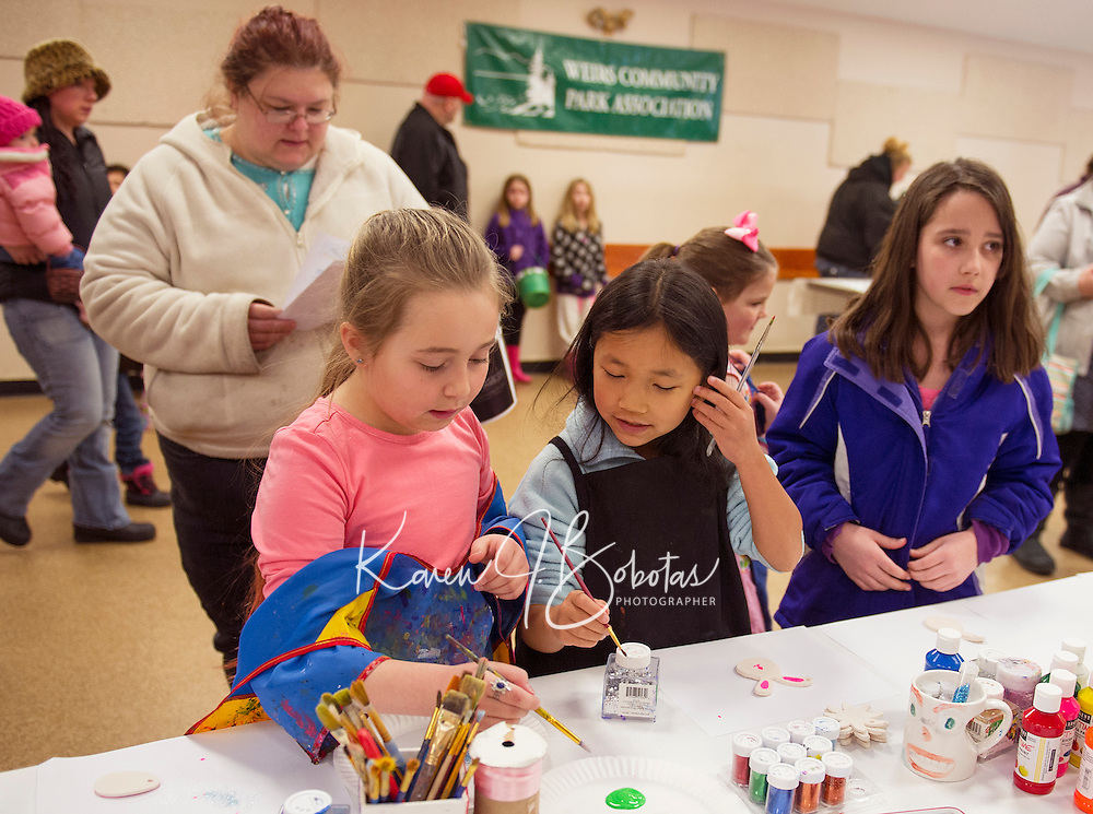Hunter Bell, Sophia Moore and Niomi Jensen paint Easter decorations at the Weirs Community Park Association's Easter fun festivities on Saturday morning.  (Karen Bobotas/for the Laconia Daily Sun)