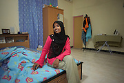 A young Muslim fisherman's wife smiles while sitting on the bed of her rented bungalow on Himmafushi factory island, Maldives..