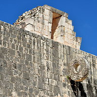 Great Ballcourt Stone Ring at Chichen Itza, Mexico<br /> On both sides of the Great Ballcourt is a stone ring decorated with a bas-relief of a serpent. The object of the sport (pitz) was to score by sending a rubber ball through this hoop. This rarely happened for several reasons. The ball weighed up to nine pounds and was typically 10 to 12 inches in diameter, nearly the size of the opening. The ring was attached to the masonry apron at a height of 20 feet. The two teams of up to six players each were immensely competitive. Most challenging of all: the athletics could not use their hands. Instead, they used their hips to forward the ball. Above the ring is a small temple. The two at the Great Ballcourt are dedicated to the sun and the moon.