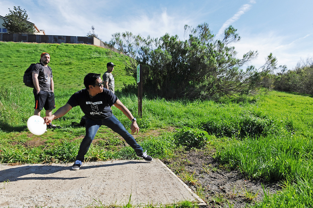 Scott Kumamura drives from the 15th hole at The Stadium disc golf course at Natividad Creek Park in Salinas. He is playing with his older brother Alan, and Matthew Cassady, at left.