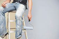 Man sitting on ladder holding paint roller low section