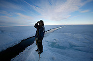 Tomi Salovinik 19  observer the ice for Seals during a seals hunt  next to a crack in the ice of Resolut Bay  Tuesday June 12 2007..Tomi Salovinik 19 hunting seals for food, every part of the seals is used or for food or for worm cloth.....