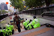 Junger Mann an einem von koreanischen Polizisten bewachten Ausgang der Metro im Zentrum der koreanischen Metropole waehrend der Feierlichkeiten von Buddhas Geburtstag (2. Mai 2009) im Zentrum der koreanischen Metropole Seoul. <br /> <br /> Young man leaving an exit of the Seoul metro protected by police man on the day of Buddhas birthday (2nd of May 2009) in the center of the Korean metropolis Seoul.