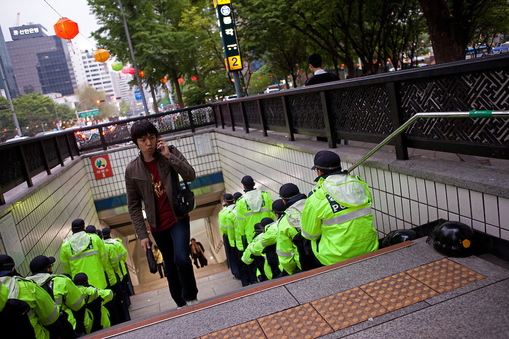 Junger Mann an einem von koreanischen Polizisten bewachten Ausgang der Metro im Zentrum der koreanischen Metropole waehrend der Feierlichkeiten von Buddhas Geburtstag (2. Mai 2009) im Zentrum der koreanischen Metropole Seoul. <br /> <br /> Young man leaving an exit of the Seoul metro protected by police man on the day of Buddhas birthday (2nd of May 2009) in the center of the Korean metropolis Seoul.