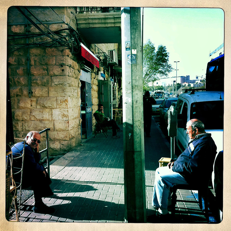 Old men sit in the afternoon sun outside of their shops in Jerusalem, Israel