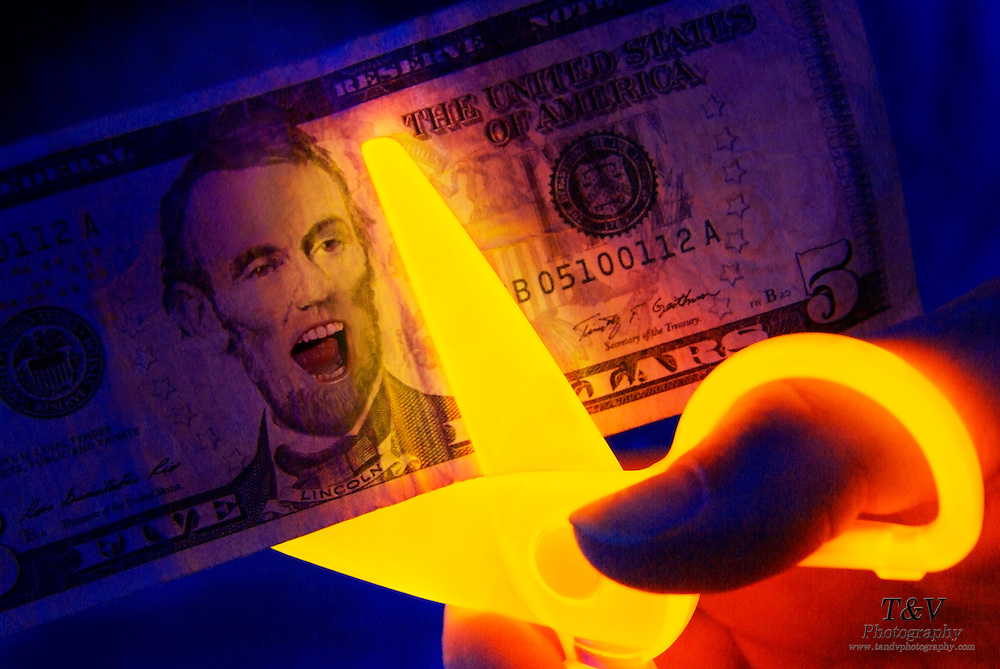 Abraham Lincoln screams as a glowing scissors cuts across a 5 dollar bill.Black light