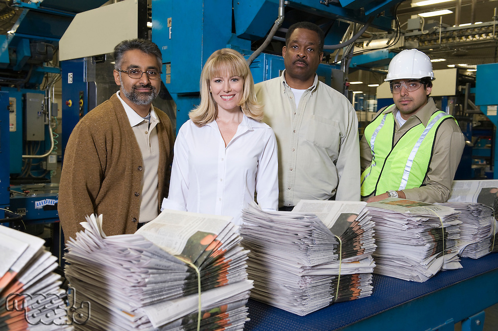 Group of people working in newspaper factory portrait