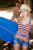 Young woman carrying surfboard outdoors half length