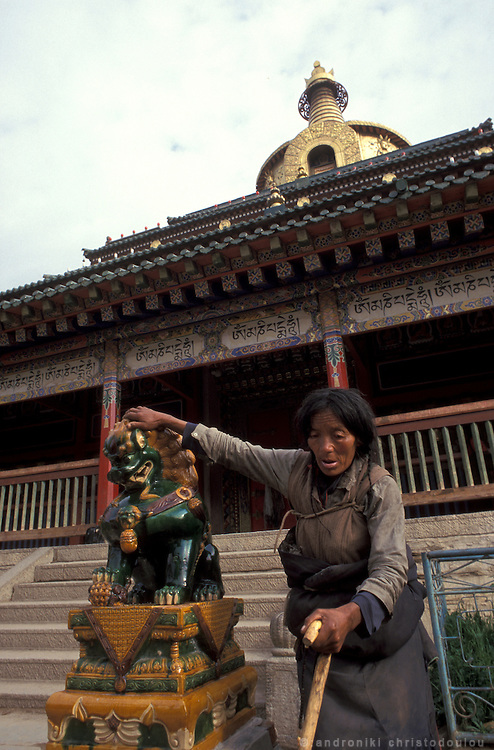 Touching the holly statues for bliss is part of the pilgrimage..LAMBRANG MONASTERY IN XIAHE - CHINA.copyright: Androniki Christodoulou.