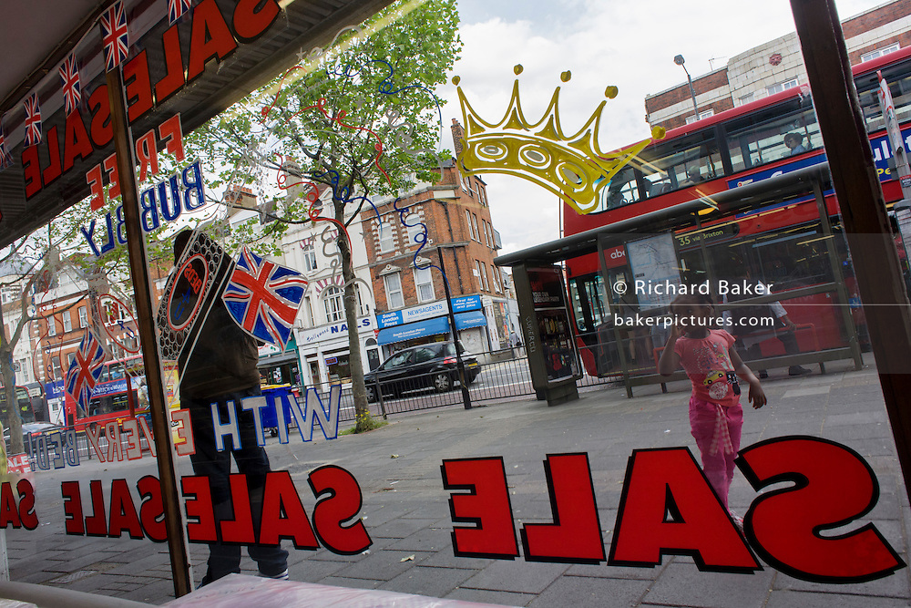 Days before the Queen's diamond Jubilee weekend, a display of patriotic flags and promotional sale offers of free bubbly adorn the window of a bedding shop in south London.
